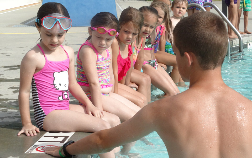 Man teaching group of girls Swim Lessons at Otter Creek Waterpark